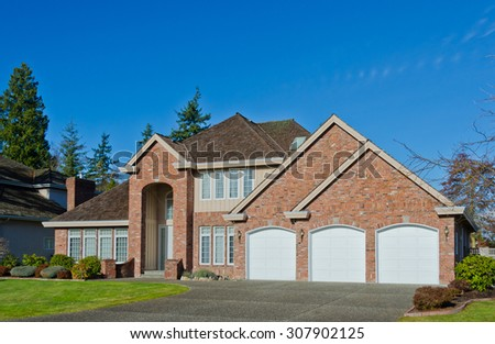 Custom built luxury house with nicely trimmed front yard, lawn and garage in a residential neighborhood. Vancouver Canada. - stock photo