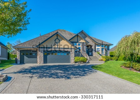 Custom built luxury house with nicely trimmed front yard, lawn and long driveway to garage in a residential neighborhood. Vancouver Canada. - stock photo