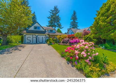 Custom built luxury house with nicely trimmed front yard, lawn and long driveway to the garage in a residential neighborhood. Vancouver, Canada. - stock photo