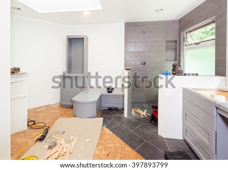 Custom cabinets being screwed into place in master bathroom - stock photo
