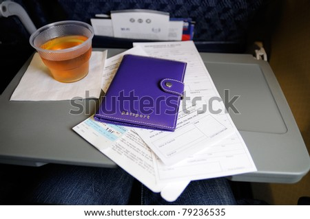 Custom forms and passport on the seat tray aboard an airline flight - stock photo