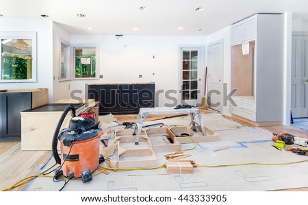 Custom kitchen cabinets in various stages of installation; base for island in center - stock photo