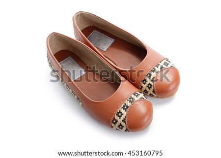 Custom made casual female footwear of orange colored leather and braided rattan, displayed on isolated white space