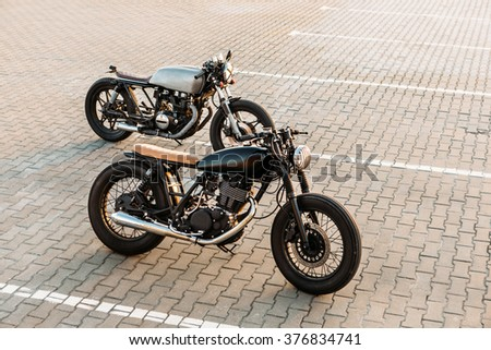 Custom vintage motorbike caferacer motorcycle with lamp lights turned on. One with grill headlight another with tape cross over optic on empty rooftop parking lot during sunset. Urban lifestyle.