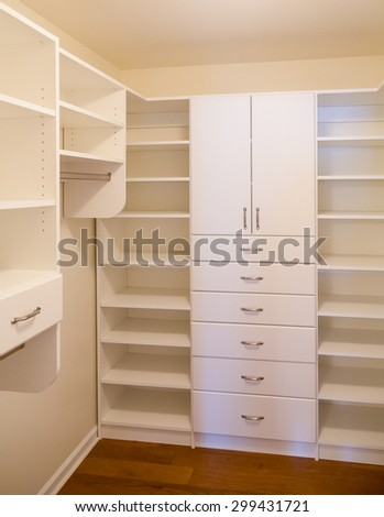 Custom white wood cabinetry in a walk in closet