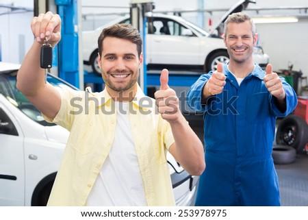 Customer and mechanic smiling at camera at the repair garage - stock photo