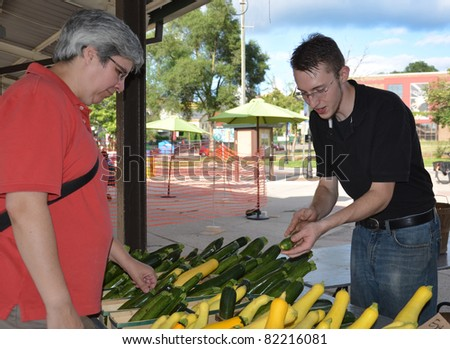 Customer and seller discussing zucchinis at the farmers market