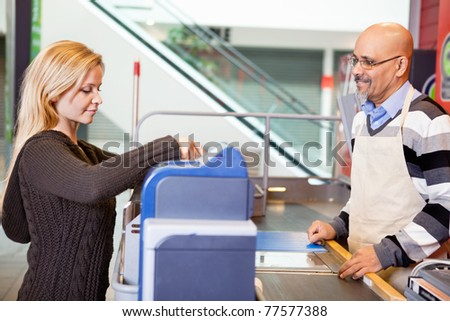 Customer and shop assistant at supermarket - stock photo