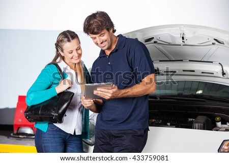 Customer And Technician Using Digital Tablet By Car