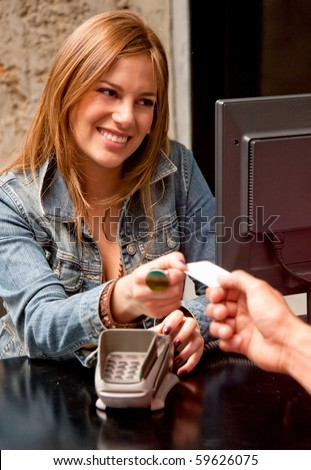 Customer at the till paying by debit or credit card - stock photo
