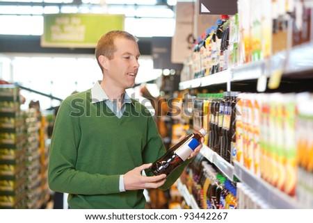 Customer buying bottle of juice in the supermarket - stock photo