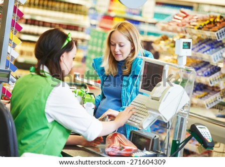 Customer buying food at supermarket and making check out with cashdesk worker in store - stock photo