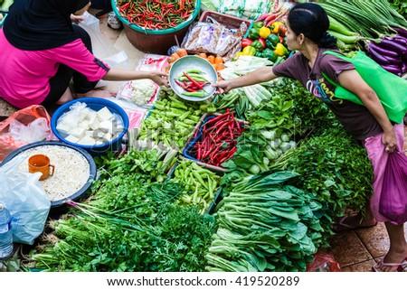 Customer buys food on the vegetable market - stock photo