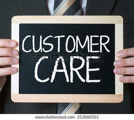 Customer care . Business man holding board on the background with business word  - stock photo