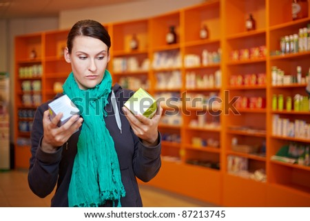 Customer doing a price comparison in a pharmacy - stock photo