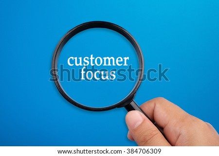 Customer focus, business concepts. Hand holding magnifying glass focusing on the words. - stock photo