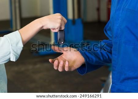 Customer giving her car keys to mechanic at the repair garage - stock photo