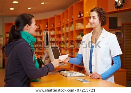 Customer giving medical prescription to pharmacist in a pharmacy - stock photo