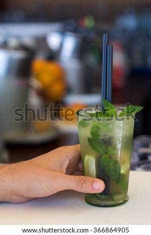Customer holding mojito cocktail on bar