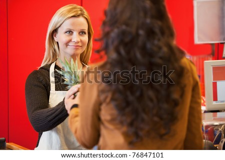 Customer holding pineapple with shop assistant in the supermarket - stock photo