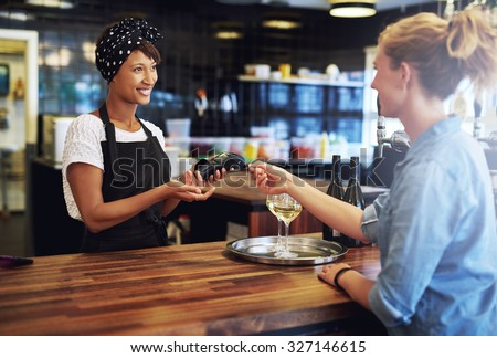 Customer in a pub paying the business owner or waitress with a credit card to be processed on a handheld banking machine, focus to the attractive African American owner - stock photo