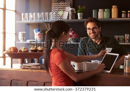 Customer In Coffee Shop Paying Using Digital Tablet Reader - stock photo