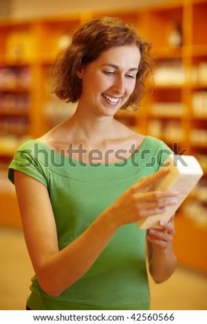 Customer in pharmacy reading information in medicine - stock photo