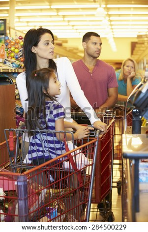 Customer In Queue To Pay For Shopping At Supermarket Checkout - stock photo
