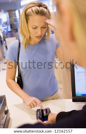 Customer in store struggling to remember PIN number - stock photo