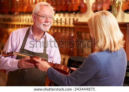 Customer Leaving Violin For Repair In Shop - stock photo