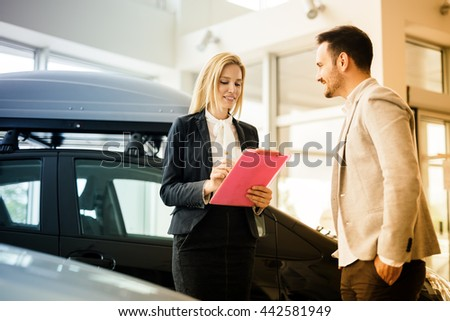 Customer looking at cars at dealership and talking to salesperson - stock photo