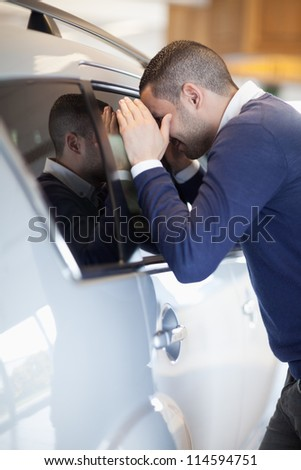 Customer looking inside a car in a garage - stock photo