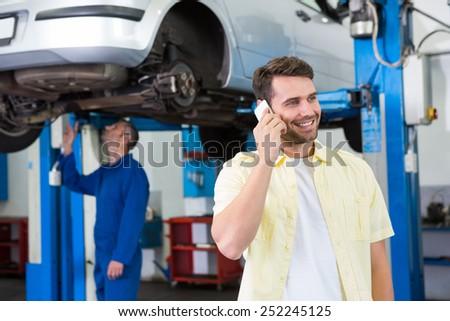 Customer making a phone call at the repair garage - stock photo