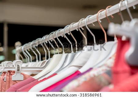 Customer or seller hand holding a hanger with clothes. Clothes on hangers on a shelf in the store, shop, supermarket.  Products and service. Close up, selective focus. - stock photo