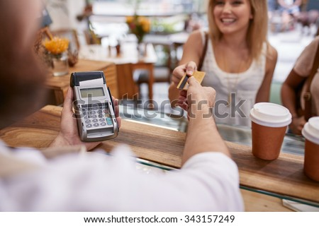 Customer paying for their order with a credit card in a cafe. Bartender holding a credit card reader machine and returning the debit card to female customer after payments. - stock photo