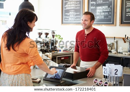 Customer Paying In Coffee Shop Using Touchscreen - stock photo