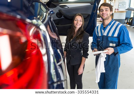 Customer picks up her serviced car in the garage and smiles with the mechanic - stock photo