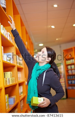 Customer reaching for product in shelf in a drugstore - stock photo