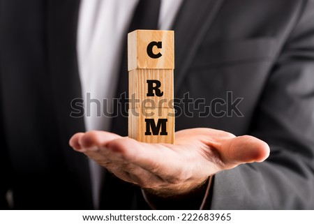 Customer Relation Management - Businessman Showing Small Wooden Blocks on Hand with CRM Acronym Texts. - stock photo