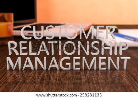 Customer Relationship Management - letters on wooden desk with laptop computer and a notebook. 3d render illustration. - stock photo