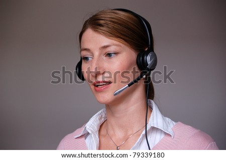 Customer Representative with headset smiling during a telephone conversation - stock photo