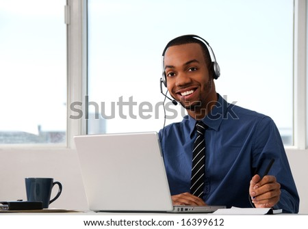 Customer Service agent in an office with laptop - stock photo
