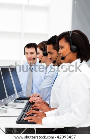 Customer service agents with headset on in a call center - stock photo