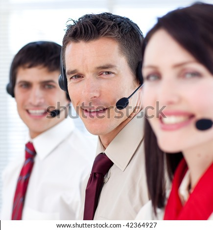 Customer service agents with headsets on in a call center - stock photo