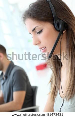 Customer service employee with headphones on - stock photo