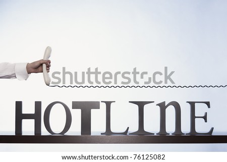 Customer service line represented by hand holding phone receiver with telephone cable above hotline letters on desk, with plenty of copy-space on blank background. - stock photo