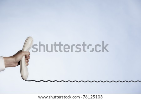 Customer service line represented by hand holding phone receiver with telephone cable, with plenty of copy-space isolated on blue background. - stock photo