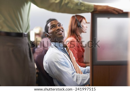 Customer Service Rep Talking with Coworker - stock photo
