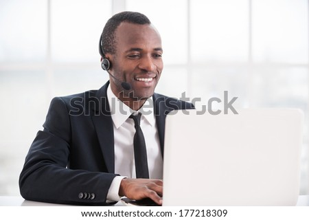 Customer service representative at work. Cheerful young African man in formalwear and headset working on laptop and smiling - stock photo