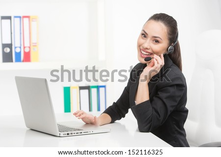 Customer service representative at work. Cheerful young customer service representative working at the computer and smiling - stock photo